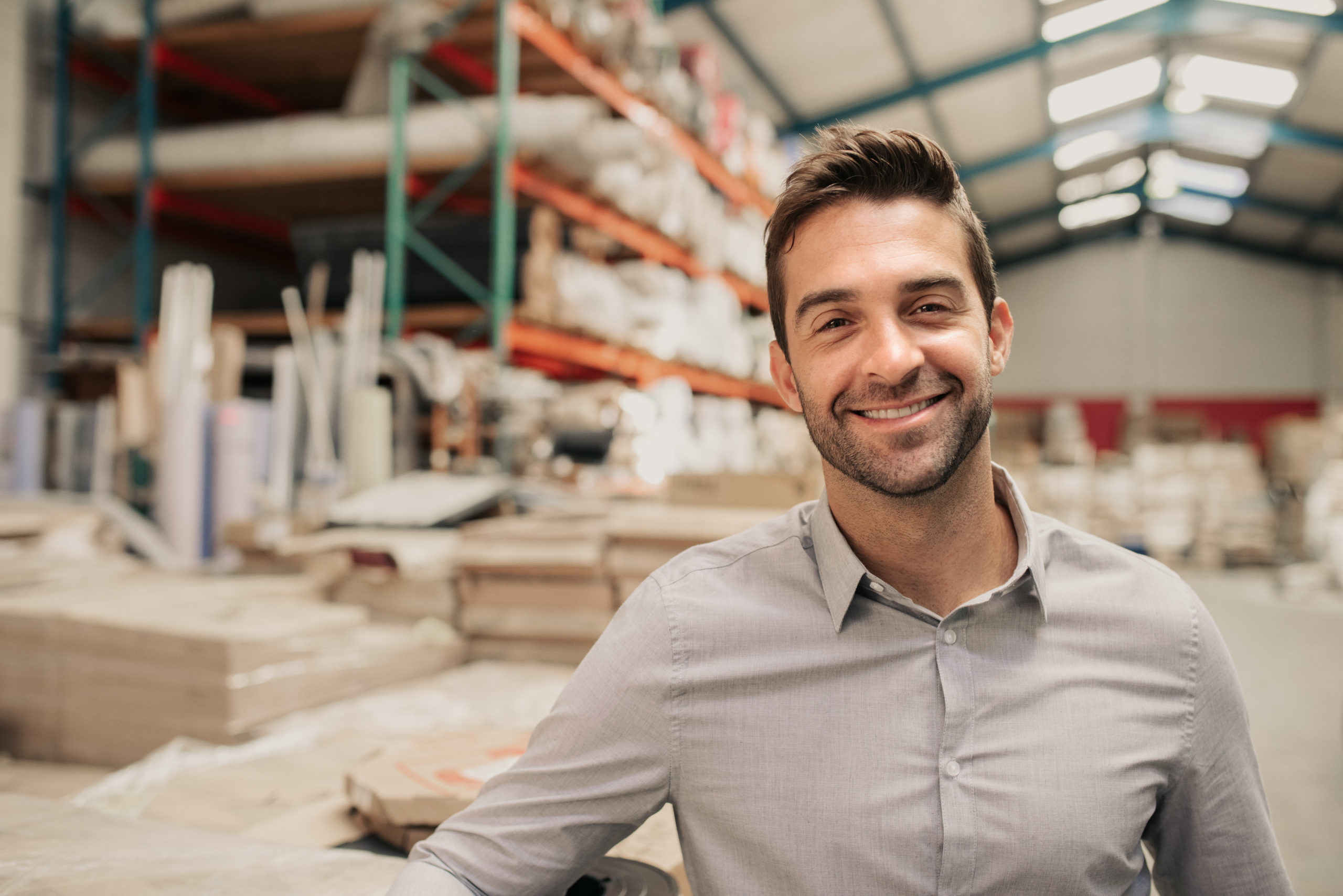 Portrait of a smiling warehouse manager leaning against some stock with stacks of carpets on shelves in the background