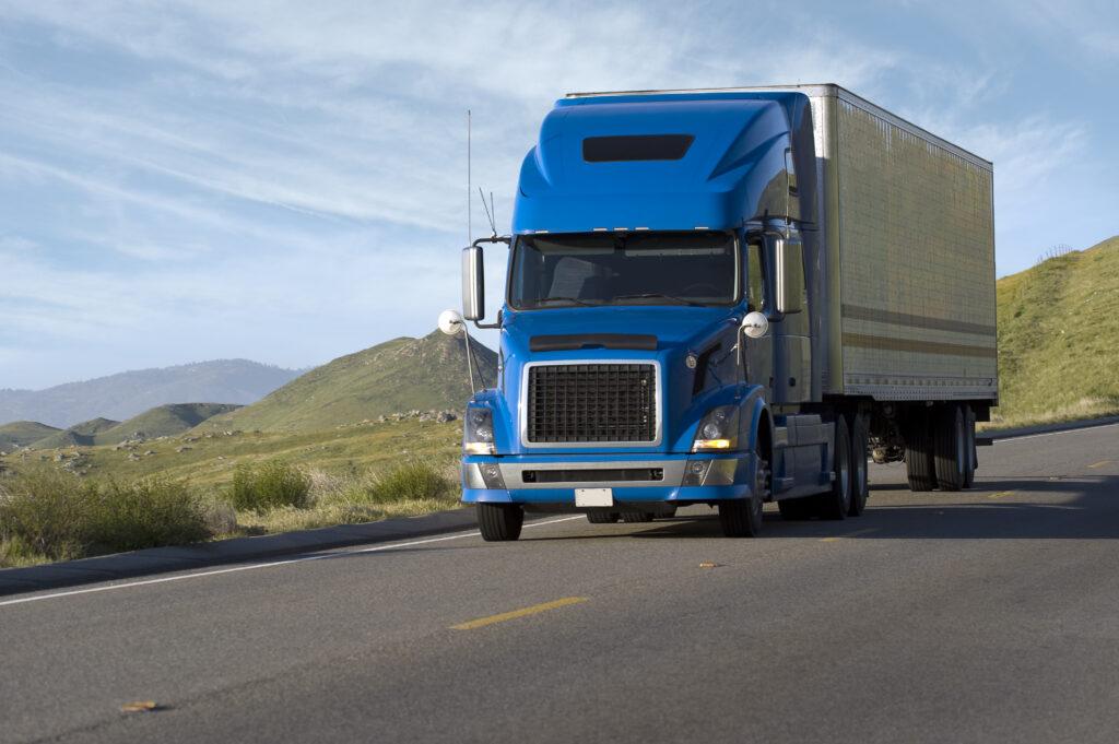 Blue modern semi truck reefer trailer carry cargo on highway