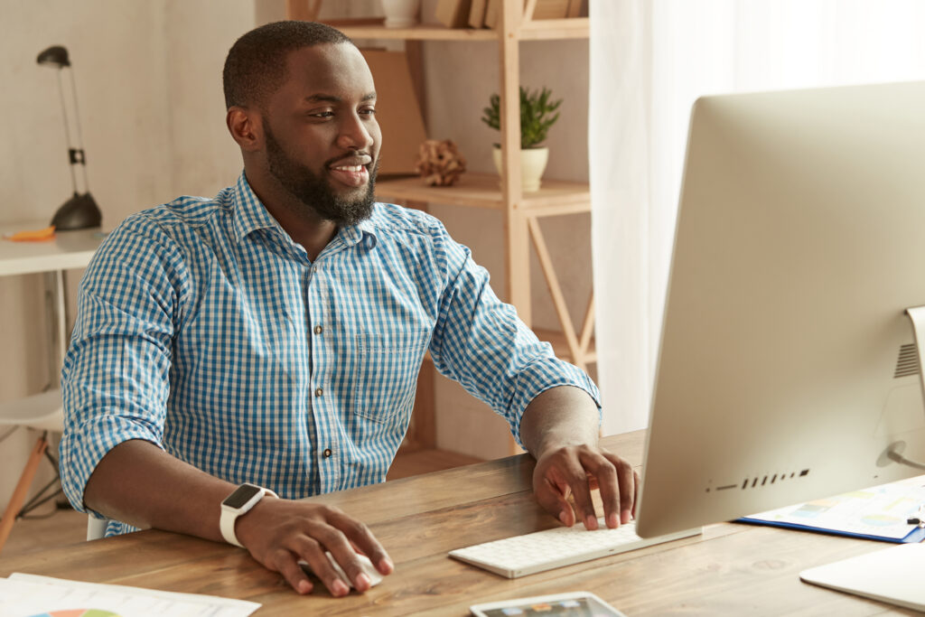 Successful businessman working remotely. Smart young afro american man in shirt working on the computer while sitting at his working place at home. Freelance. Home office workplace